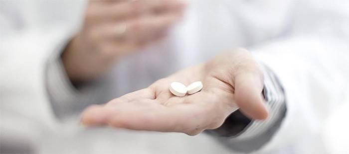 Мужчина держит таблетки Трихопол