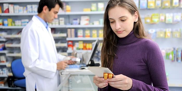 Девушка в аптеке покупает лекарство