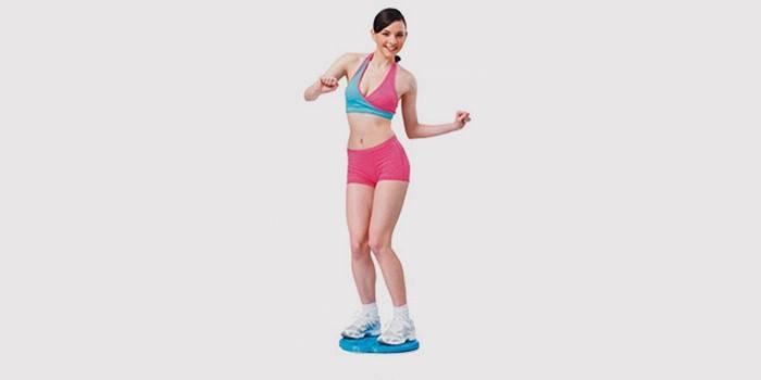 Девушка делает упражнение на диске здоровья для талии и живота