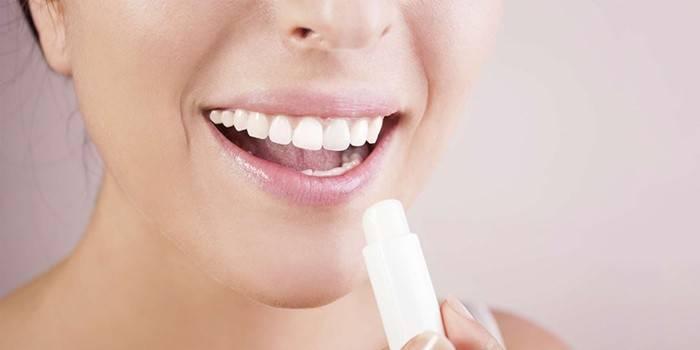 Девушка мажет губы гигиенической помадой
