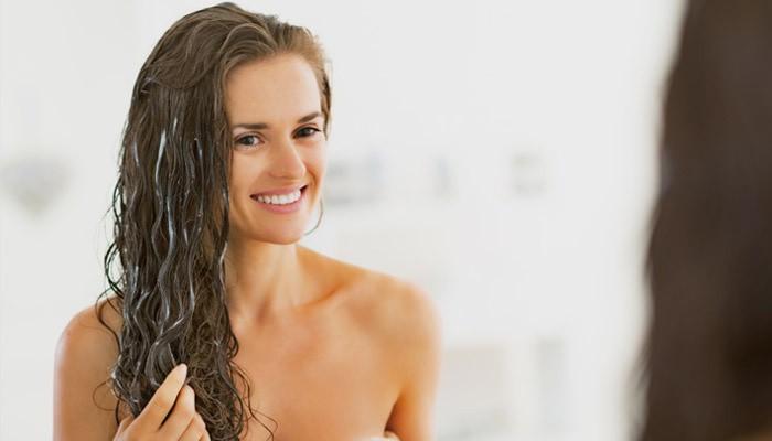 Женщина наносит маску для роста волос