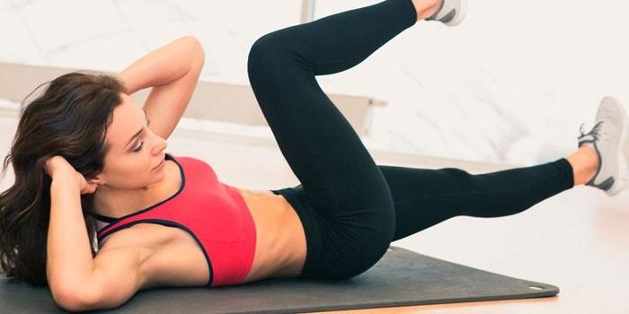 Девушка делает упражнение скручивание лежа на спине