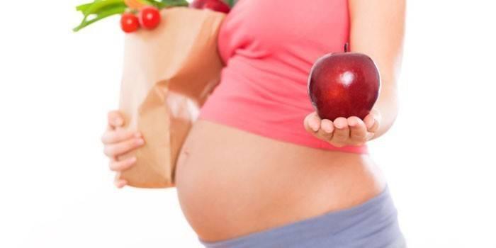 Беременная девушка держит яблоко на ладони