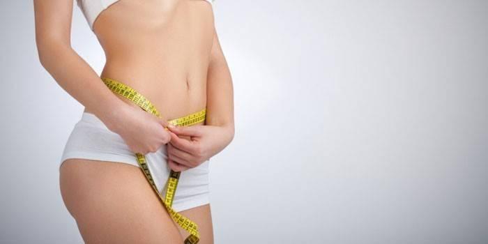 Девушка измеряет объем талии сантиметром объем талии