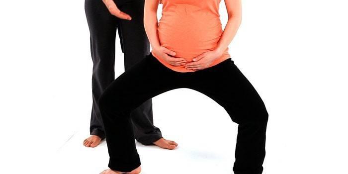 Беременная девушка приседает