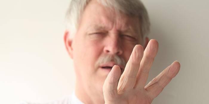 Пожилой мужчина смотрит на пальцы рук