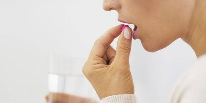 Женщина принимает таблетку