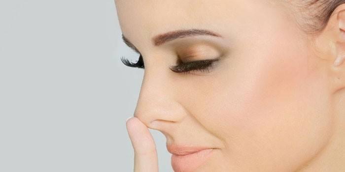 Девушка задирает пальцем кончик носа
