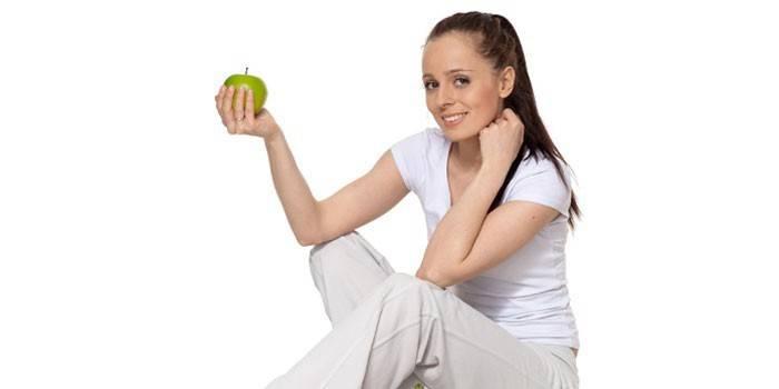 Девушка держит в руке яблоко