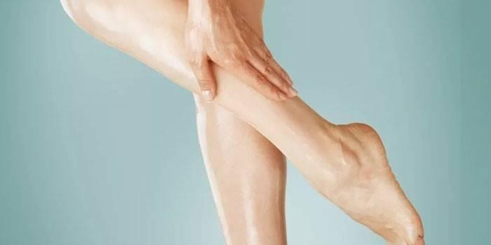 Женщина гладит ногу рукой