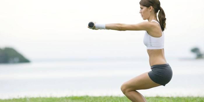 Девушка делает упражнение Стульчик с гантелями