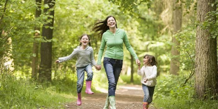 Женщина с детьми на прогулке в лесу