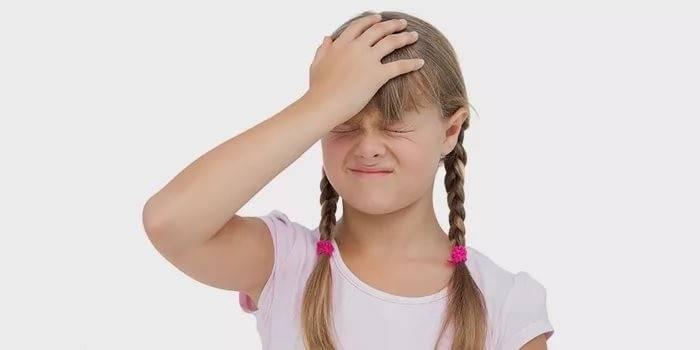 Девочка держится рукой за голову