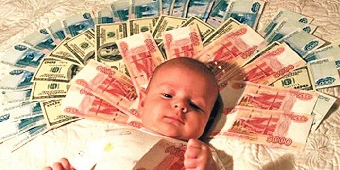 Младенец лежит на денежных купюрах
