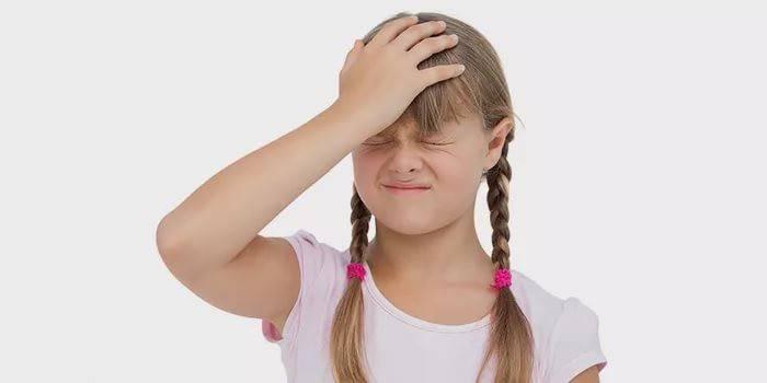 Девочка держится рукой за лоб