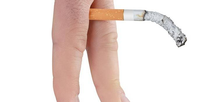 Тлеющая сигарета между пальцев