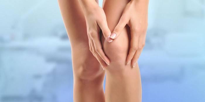 Девушка держится руками за колено