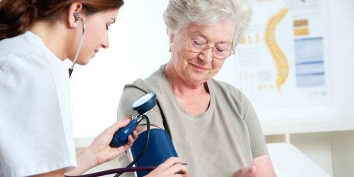Медик измеряет артериальной давление у пожилой женщины